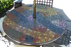 My mosaic patio table with ribbons of color and black grout. The base is hardie-backer and plywood. kim*