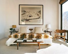The light-filled living room features a Jean-Michel Frank sofa, Hans Wegner hoop chairs, luxurious fur throws, and exhilarating views over Aspen Mountain.  Photographed by François Halard (originally in Vogue)