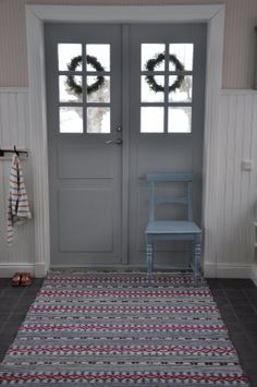 Swedish Entry hall with rug in rosepath pattern and a Pippi Longstocking sweater languishing on a hook.