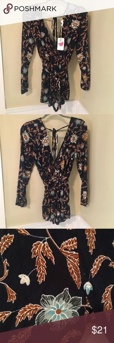 L'ATISTE by Amy NWT floral romper, size Medium NWT L'ATISTE by Amy floral romper, size medium. Has a deep crossed neckline, ties around the waist and at the top of the back. Navy blue floral. l'atiste Dresses Mini