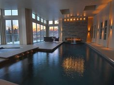 An expansive indoor swimming pool with waterfall feature, bridge, and retractable exterior...