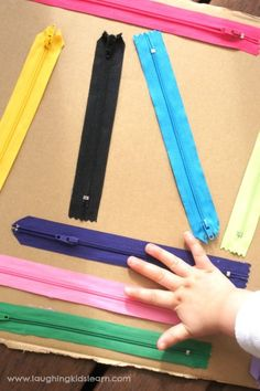 Playing with a handmade sensory board using zippers