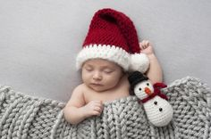 Sleeping, two week old, newborn, baby boy wearing a crocheted Santa hat with snowman plush toy.