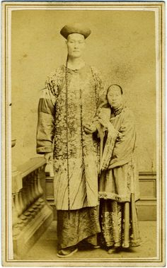 """Albumen photograph carte de visite of """"Chang the Chinese giant"""" (Zhan Shichai) and his wife, Kin Foo, who accompanied Zhan from China; both dressed in ornate Chinese clothing, and Chang with a traditional upturned hat. (c. 1871)"""