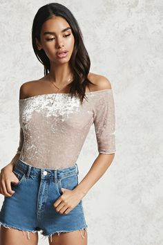 A knit crushed velvet top featuring an off-the-shoulder neckline, short sleeves, and a cropped silhouette.