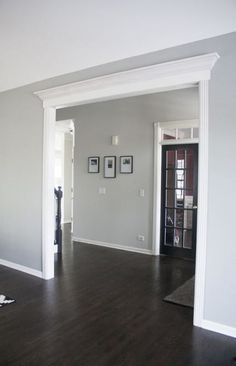 I LOVE the dark wood floors and the light grey walls/white trim. I also like how the entryway is framed and crown moulding added. Home makeover ideas! wood floors grey walls Home Tour Living Room Wood Floor, Living Room Grey, Living Room Decor, Living Rooms, Living Room Ideas With Dark Wood Floors, Living Room Hardwood Floors, Dining Room Paint, Bedroom Flooring, Benjamin Moore Grey Owl