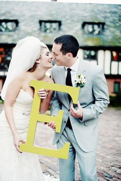 Bride and groom holding the first letter of the last name they share now. Liking this more than the