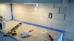 Finally putting up the backsplash! 4x16 subway tile in gloss white.