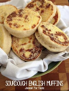 Sourdough English Muffins in a white napkin in a green bowl on a wooden cutting board.