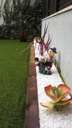 Césped artificial con traviesa de tren. piedras blancas y decoración y plantas