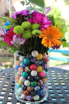 love love love the idea of filling vases with bouncy balls (even w/out the flowers) for centerpieces...maybe for spoons/forks holder, etc.??