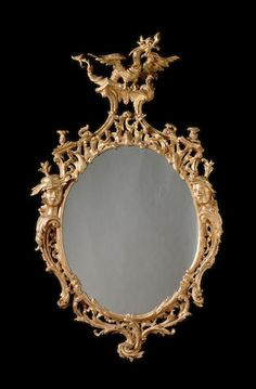 A George III carved giltwood Mirror, after a design by Thomas Johnson, the later oval plate with a pierced rocaille frame flanked to each side with masks of chinamen on 'C' scrolls and acanthus leaves surmounted by a dragon cresting, with pierced leaf cresting, with pierced leaf carved apron below