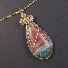 Sunset At Sea Agate Gold Filled Wire Wrapped Pendant   Wonderful wire wrapped pendant with a layered agate that looks like a picture of rough seas just after a storm at sunset. Glorious colors! Wrapped in 14k gold-filled wire. A gold plated twisted rope chain is included in your choice of length. Each chain is hand assembled with a gold filled clasp, links and coordinating beads or crystals in each link. Please include your custom length in the note to seller or send me an email.   The…