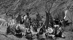 Stock Footage B/W 1800s wide shot Native Americans sitting in circle with man speaking   gesturing / teepees in background  Download using the VidLib app. 50.000 Royalty Free Clips