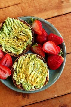 Whole grain English muffin topped with mashed avocado, salt + pepper, and nutritional yeast with a side of fresh strawberries.