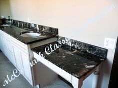 This extended bathroom counter is even further extended with the vanity attached to the end. An elegant black marble granite adds a lot to the counter.