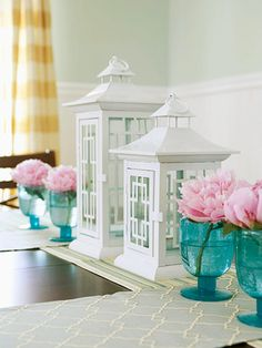 Tiny glasses transform into single vases for a classic centerpiece display.  I have teal glass, I like to show it in the summer, and I have a display case in my hall entry filled with it.