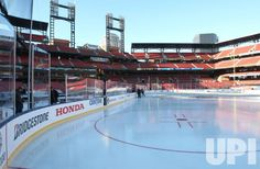 Workers examine the new ice on a ice rink installed inside Busch Stadium in St. Louis on December 29, 2016. The St. Louis Blues will host…