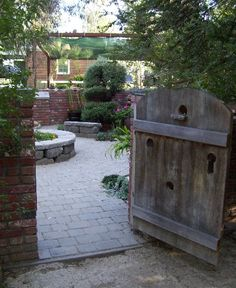 Patio Design Ideas: Patio Passageway: A brick wall completely surrounds this patio and a wooden gate allows visitors into an area that is intended to be private. For additional privacy, you would want to close and lock the gate, especially when you're not at home.