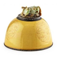 YELLOW GLAZED BEEHIVE WATER POT MOUNTED AS AN INKWELL THE PORCELAIN KANGXI PERIOD, MOUNTED BY EDWARD FARMER the porcelain body incised with three roundels formed by a coiling dragon, mounted in silver with a hinged cover surmounted by a jadeite lotus leaf, interior with silver inkwell. The white glazed base bearing a six-character underglaze blue Kangxi reign mark. Impressed silver mark reading EDWARD FARMER INC STERLING 12.5cm diam.