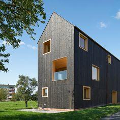 Blackened timber house by Bernardo Bader Architekten stands on the edge of a stream