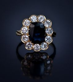 An Antique Russian Sapphire and Diamond Engagement Ring made in St. Petersburg  between 1908 and 1917 A natural midnight blue sapphire in a claw setting with an approximate weight of 2.6 ct, encircled by 11 Old European cut diamonds with an approximate total weight of 2.05 carats (color F-G, average clarity VS2-SI1).Height 18 mm (11/16 in.)Marked with 56 zolotniks old Russian gold standard (14K - 583) / St Petersburg assay office, and master's initials.
