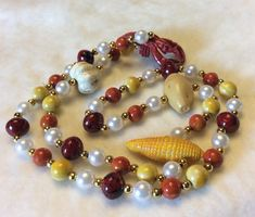 Wonderful and fun acrylic beaded necklace. Specialty beads include a lobster, garlic, corn on the cob, potato. Marbled and imitation Pearl beads with gold metal spacers. Excellent condition. Great gift for lobster lover, or beach party. Measures 36 inches overall. No closure. Thanks for looking  Please visit my other vintage jewelry and misc items shops: http://www.garagesale715.etsy.com http://www.tendollarjewelry1.etsy.com http://www.jewelry715.etsy.com thanks ...