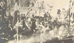 Κυριακή 1η Δεκεμβρίου 1913 *...είναι ακριβώς η στιγμή που ο βασιλέας Κωνσταντίνος και ο πρωθυπουργός Ελευθέριος Βενιζέλος ετοιμάζονται να παραδώσουν τη σημαία στους γηραιούς αγωνιστές Αναγνώστη Μάντακα και Χατζημιχάλη Γιάνναρη προκειμένου να την υψώσουν στον πιο ψηλό ιστό. Στο μέσο περίπου της φωτογραφίας και λίγο προς τα αριστερά διακρίνουμε τον μονάρχη Κωνσταντίνο και αριστερά του, με το ημίψηλο καπέλο, τον Ελευθέριο Βενιζέλο, ντυμένο επίσημα, όπως απαιτούσε η στιγμή. Στα δεξιά του ...