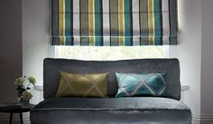 James Hare -  Evolution Fabric Collection - Aqua and olive green patterned cushions, a matching striped window blind, aplain grey sofa, a round table and a vase