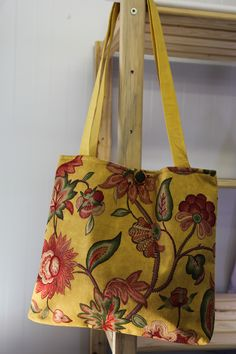 Stunning colors and beautiful floral patterns with a simple button closure.  This bag is one of a kind! Designed and handmade with love at Siyazenzela!