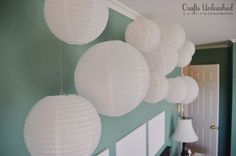 Create a Fun & Whimsical Wall Installation with Paper Lanterns  relatively cheap and no need wiring, by using battery operated tea lights.
