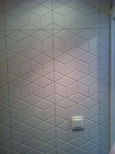 white geometric tiles in a bathroom..but with dark grout..just an identical diamond at different angles