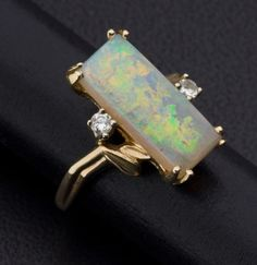 The ring features a rectangle-shaped opal measuring 17.35 x 7.80 mm, enhanced by full-cut diamonds weighing a total of approximatley 0.10 carat, set in 14k gold. Gross weight 6.50 grams.