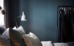 Detalle de un dormitorio con una pared pintada de oscuro, con un colgador, una cama y una mesilla de noche.