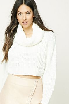 A chunky, ribbed knit crop sweater featuring a cowl neck, long raglan sleeves, and a boxy silhouette.