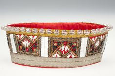 Child's crown using traditional Latvian patterns from the Nica region. It was woven by Anna Apinis in the 1960s for her daughter Anita. Anna Apinis was born in 1913 in Latvia. She attended weaving lessons in Liepaja in Latvia from 1930 to 1933 and spent hours at the nearby Liepaja Ethnographic Museum, recording traditional fabric designs in her notebooks.