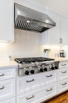 Chic white kitchen features white shaker cabinets paired with white quartz countertops and a white herringbone tile backsplash.