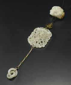 A CELADON JADE PENDANT  QING DYNASTY comprising three elements; a pebble form carving of a chilong coiled around a lingzhi; an openwork plaque with a bat, chime and the characters ping an and two interlocking rings