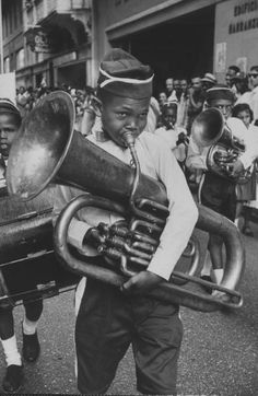 Young boy playing the tuba during a parade. Photograph by Hank Walker. Dominican Republic, December 1959.