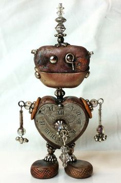 This unique little Steampunk Robot stands about 4 inches tall. He was assembled from polymer clay, bits of metal and Swarovski crystals.
