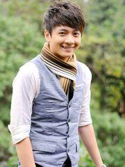 Hình ảnh ca sĩ Ngô Kiến Huy đẹp trai phong độ với phong cách thời trang mới, với áo sơ mi trắng và gile màu ghi, cùng với khăn quàng kẻ