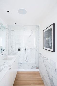 Minimalist bathroom with a marble shower, wood floors, and a floating sink