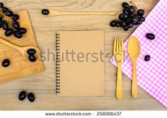 Food ingredient and kitchenware with notebook on wooden background