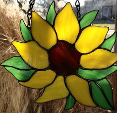 This glass is a must see in person! Guaranteed to put a smile on your face. Stained glass sunflower measuring 8 inch wide x 9 tall . Hand crafted from yellow, green and brown spectrum glass with black patina on solder. Comes with black jack chain to hang Handmade in my home studio. We love custom orders. We are always available to help. Just send me a message