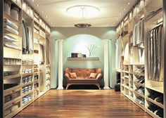 a dream closet the inviting neutral colors of cream white brown tan and teal hardwood floors lined walls of clothes great lighting a masterpiece