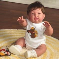 """All Berenguer dolls are made in Spain.    Part of the Baby Moments Collection,""""Reaching for Love"""" is trying to get to his favorite toy. This precious baby moment is captured in his curious expression and his chubby, outstretched arms. He is just waiting for you to pick him up!"""