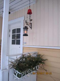 Jouluvalot ja itsetehty tuulikello kävyistä ja helmistä.