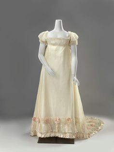 1812 Beautiful cream sheer satin and lace wedding dress, trimmed with peach colour flowers at the hem.
