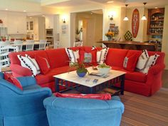 Entertain in style with this coastal living room, complete with bright blue chairs, a red wraparound sofa, and a white and blue coffee table on a striped rug. Prepare cocktails from your mahogany bar off to the right, or grab a snack from the  kitchen, boasting a marble counter top and plenty of seating.
