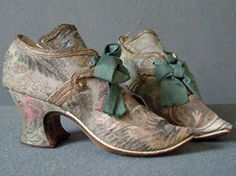 Shoes, English, c. early 1730's. Made of silver gilt woven with pink and coral flowers, green and silver leaves and gold circles. The deep tongues have curving top edges, lined with pale blue finely ribbed silk. The latchets are tied with green silk grosgrain ribbons. The shoes are lined with white kid leather, and the soles are of brown leather.